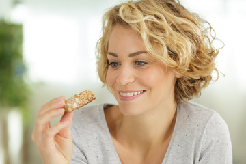 attractive lady holding a cereal bar