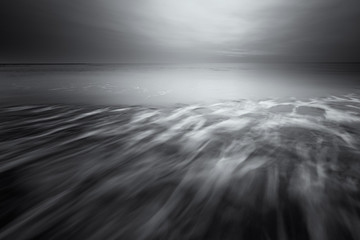 A fine art seascape landscape in black and white of the beach with waves and dark clouds