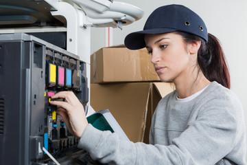 young female technician fixing a printer