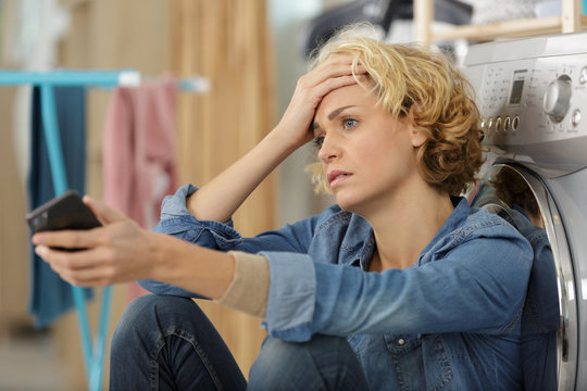 distressed woman holding smartphone leaning against washing machine