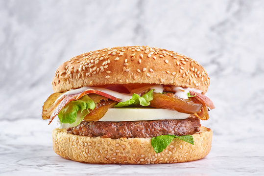 burger with big beef cutlet, mozzarella cheese, bacon, mint and figs isolated at white marble background.