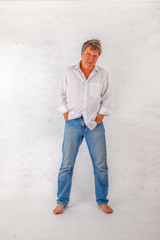 Mature man standing up against a white background