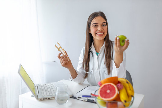 Young female nutritionist sitting at table with fresh vegetables and fruits in her office. Female nutritionist sitting at table with clipboard and healthy products on white background