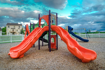 Colorful slides and swings on a neighborhood playground under cloudy blue sky