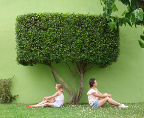 mom and daughter are sitting under a green tree