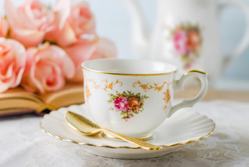 Cup of tea with book, teapot and rose flowers on blue background with vintage tone - Afternoon tea party concept