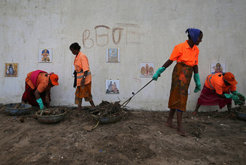 Workers remove garbage from the Juhu beach in front of a wall with religious pictures in Mumbai