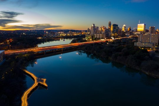 Long exposure aerial photo of the Austin Texas Skyline Photo at Night with skyscrapers and the boardwalks on lady bird lake