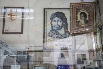 A woman's reflection is seen on the glass at a showcase of a mechanic shop in downtown Tehran