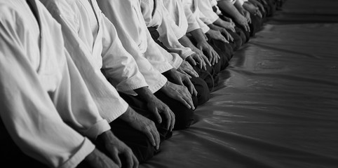 Black and white image of aikido. Men are sporsmen. Aikido workshop. A number of black belt practitioners in traditional uniform, white kimano and black hakama.
