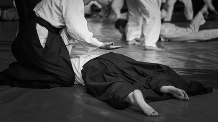 Black and white image of aikido. ?thlete girls involved in martial art of Aikido. The traditional form of clothing in Aikido.