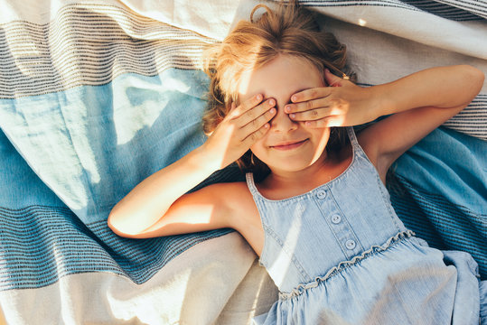 Beautiful blonde little girl lying on the blanket, cover her eyes from the sun with both hands, enjoying summer day. Adorable child having fun and plaiyng peekaboo outdoors in the park