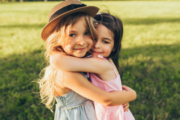 Outdoors portrait of two adorable children shares love and frienship. Two little girls playing in the park. Two sisters having fun on sunlight and nature background. Childhood and friendship concept