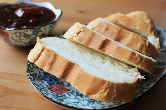 Slices of white bread on a plate on the table with plum jam
