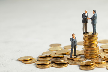 Businessmen shake hands as a symbol of a successful profitable transaction. Businessmen on a stack of gold coins as a symbol of success or successful investments