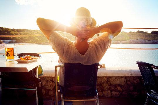 Mann entspannt sich mit Blick auf das Meer und einem Bier
