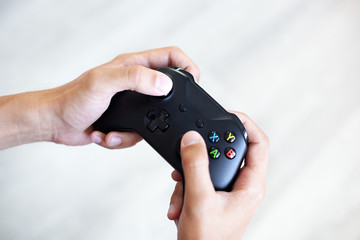 Black joystick in hands isolated on white background. The guy is playing on the console. Computer gaming technology play competition videogame control confrontation concept. Cyberspace symbol