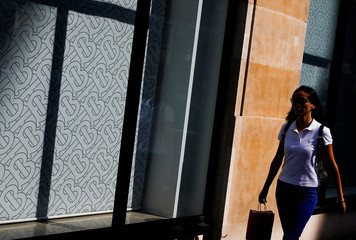 The Burberry logo is pictured at a window as a woman walks past a Burberry office in central London