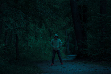 Scary dark male figure in a hoodie standing on the path in the forest with mysterious light coming behind him, night horror scene in forest