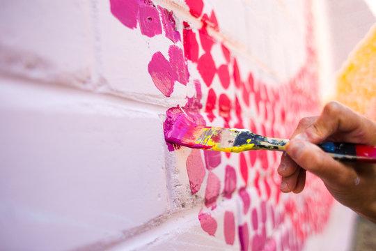 The artist draws on a brick wall.