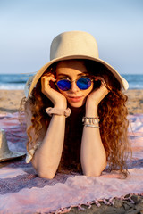 Photo sur Aluminium Chien de Crazy Young redheaded girl wearing a hat and sunglasses on a Mediterranean beach.