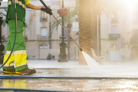 Worker cleaning the city streets with high pressure gasoline washer splashing dirt, professional cleaning services. High pressure cleaning, lower body