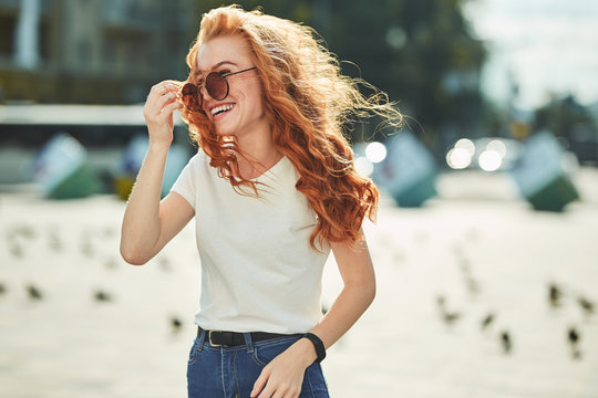 Beautiful red-haired girl having fun on the street. The girls have a beautiful figure, a white T-shirt and jeans with sunglasses