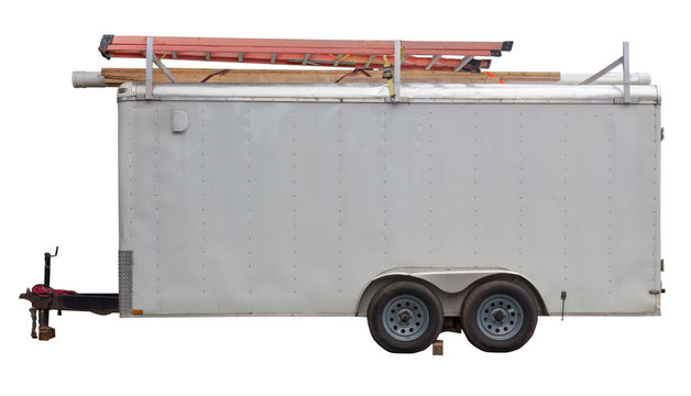Side view of older white utility work trailer parked in residential neighborhood with ladders on top.