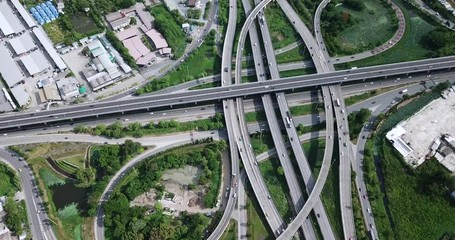 Fotobehang - 4K. Aerial view of road interchange of highway intersection with busy urban traffic speeding on the road. Junction network of transportation taken by drone.