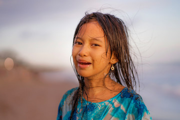 beach lifestyle portrait of young beautiful and happy 7 or 8 years old Asian American mixed child girl with wet hair enjoying holidays playing in the sea having fun