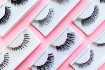 Different false eyelashes on a trendy pastel pink background. Beauty pattern. Makeup accessories. Cosmetics products for women. Bright colorful backdrop. Closeup.
