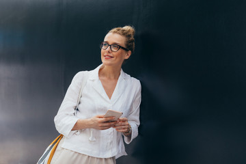 Portrait of pretty Caucasian blonde smiling woman standing by the black wall and holding her smartphone.
