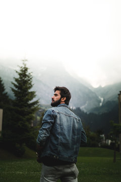 man wearing blue denim jacket standing in front of trees and mountain