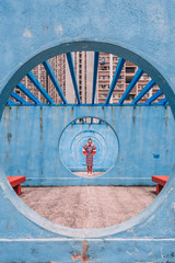 Woman standing in round blue concrete pathway