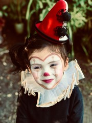 toddler girl with jester costume in close-up photo