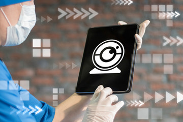 Doctor uses digital laptop with web camera icon on display. Webcam health telecommunication technology. Online doctor video medical consulting concept.