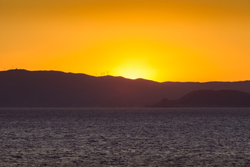 Sunset on the Saronic Gulf islands dotted with wind turbines