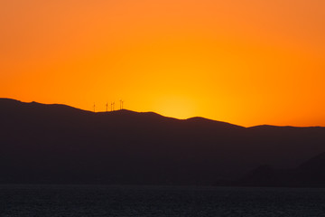 Saronic Gulf islands silhouette with wind turbines at sunset