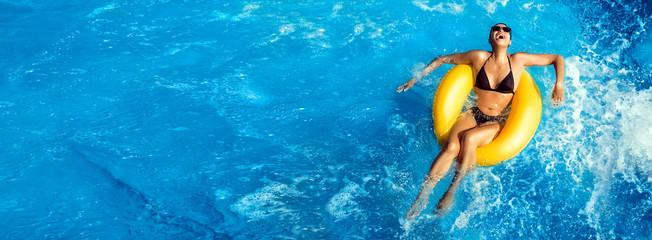 Fototapeta Summer vacation. Laughing young woman enjoying an aqua park. Fun in the pool