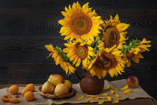 Still life with sunflowers in a clay pot and fruit on against a wooden wall.
