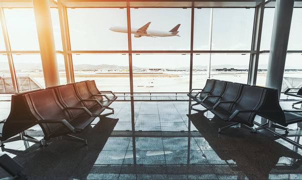 Wide-angle shot of a modern aircraft gaining the altitude outside the glass window facade of a contemporary airport terminal waiting room with rows of seats and reflections on a marble floor