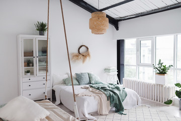 Modern scandinavian sunny bedroom with plants , floral pattern bedding and pillows. Space with white walls and wide window. Eco decor. Real photo.