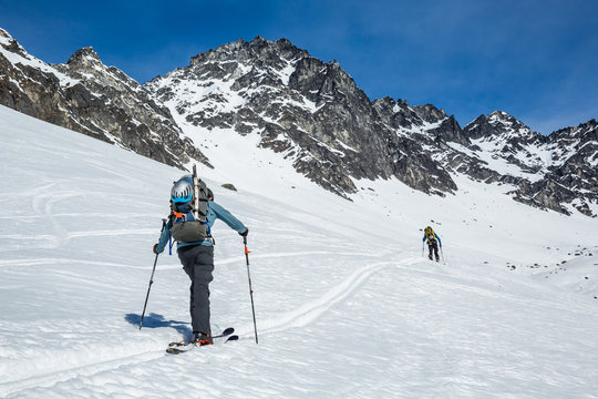 Two skiers skinning up slope near Snowbird Mine in Hatcher Pass area in the Talkeetna Mountains, Alaska.