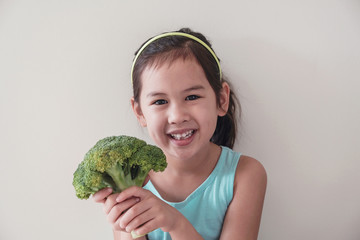 Happy and healthy mixed Asian girl holding a broccoli, child wellness, vegan healthy food concept