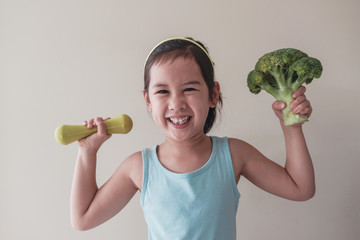 Happy and healthy mixed Asian girl lifting a broccoli and a dumbbell, child wellness concept