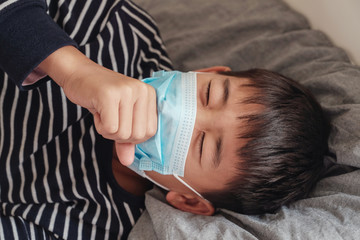Sick preteen Asian boy wearing a mask and coughing in bed