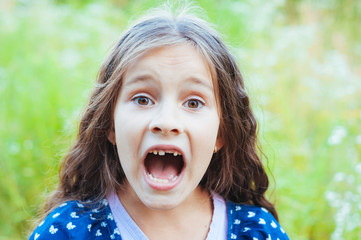 Little adorable girl screaming in the field in nature, daylight, summer Wall mural