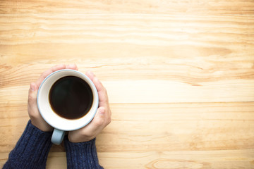 A woman wearing a blue jersey holding a cup of coffee with her hands. Place it on the wood table on...