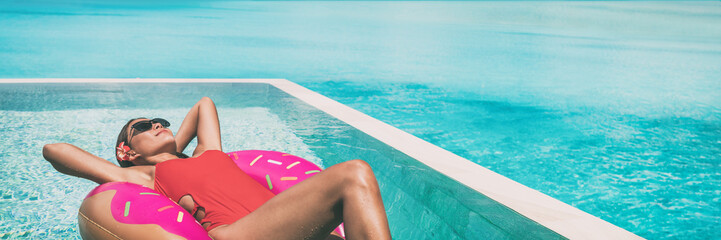 Wall Mural - Swimming pool suntan woman soaking up the sun sunbathing relaxing on donut float floating on infinity pool panoramic banner. luxury resort vacation sunbathing . Red swimsuit girl happy.