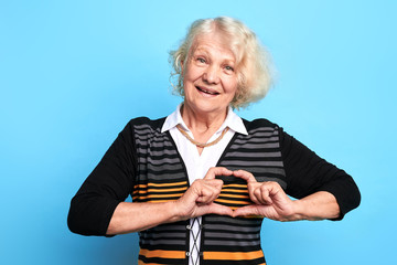 Beautiful old woman making heart gesture isolated over blue background . lady showing heart symbol and shape with hands. Romantic concept.I love you. I miss you.body language , lifestyle
